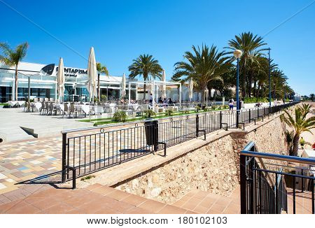 Punta Prima Spain - March 28, 2017: Tourists sitting in a seafront cafe. Punta Prima is a popular tourist place. Province of Alicante. Southern Spain
