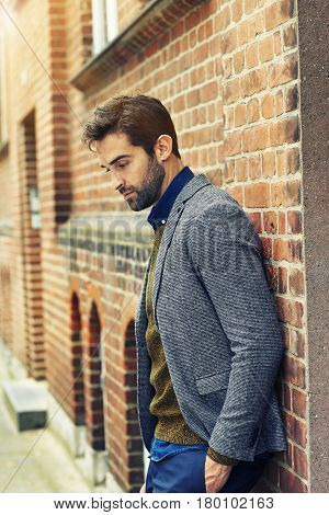 Thoughtful man in jacket leaning against wall