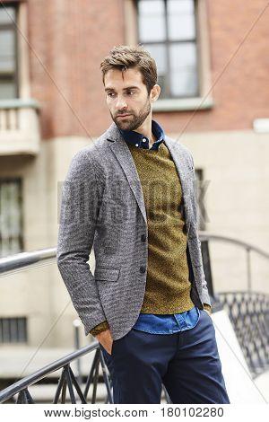 Handsome man in jacket looking away in city