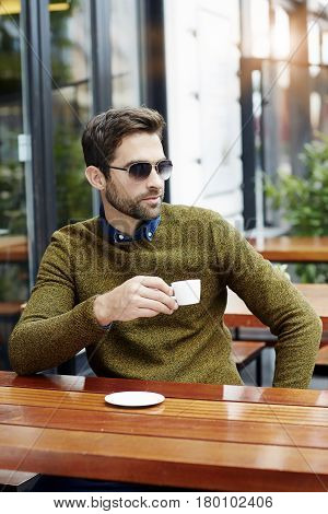 Man holding coffee cup outdoors city life