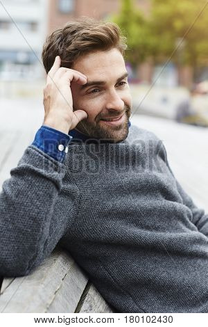 Contemplative man in grey sweater smiling city life