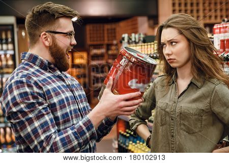 Happy Man showing keg of beer to your displeased woman while being in supermarket
