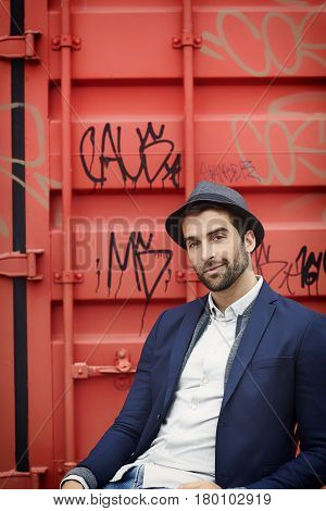 Trilby guy in front of container portrait