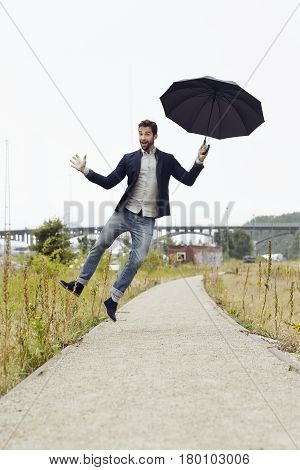 Umbrella guy jumping for joy on footpath
