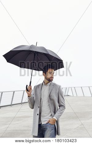 Umbrella guy in grey overcoat looking away