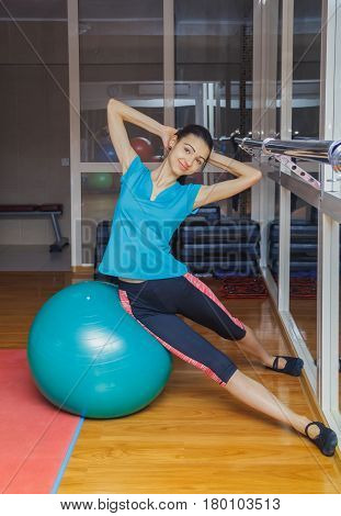 Fitness woman in gym resting on pilates ball. Young woman doing exercise on fitness ball. Young girl on the blue fitness ball in gym. Girl with fitness ball.Healthy lifestyle