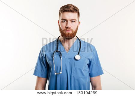 Portrait of a serious confident male doctor standing over white background