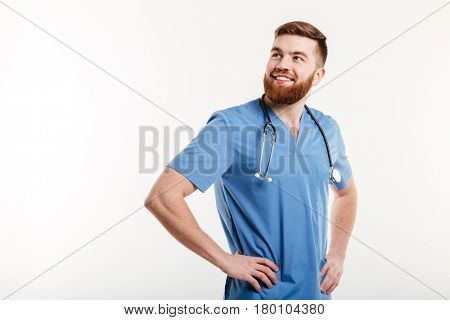 Portrait of a young smiling positive man doctor with stethoscope holding hands on hips and looking away isolated on a white background