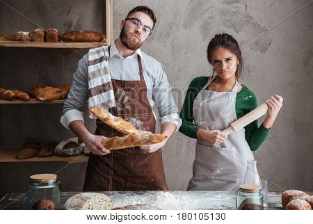 Young man with two loafs and woman with rollin pin standing in kitchen earnestly