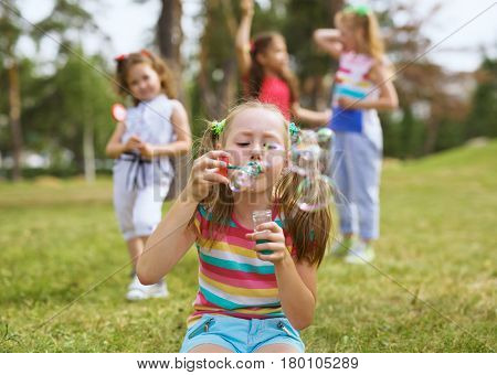 Pretty little girl with ponytails sitting on grass and blowing soap bubbles on background of her friends in park