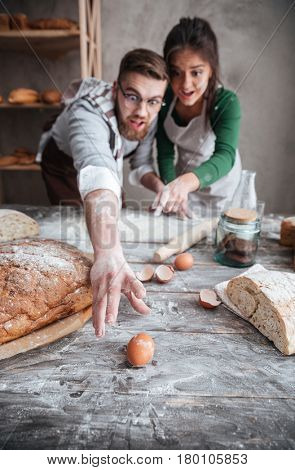 Shocked bearded man in glasses and surprised woman in apron trying to catch egg on table in kitchen