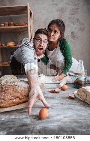 Young man and shocked woman trying to catch egg on table with flour in grey kitchen