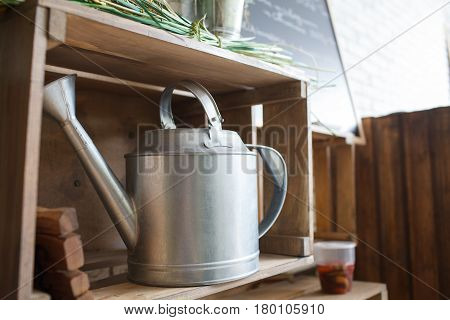 Metallic grey watering can in a wooden brown box