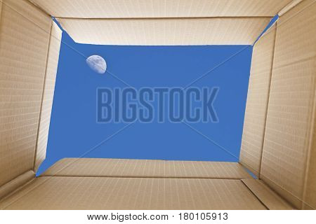 View from inside a cardboard box. Full-moon in the sky outside the box. Freedom concept.