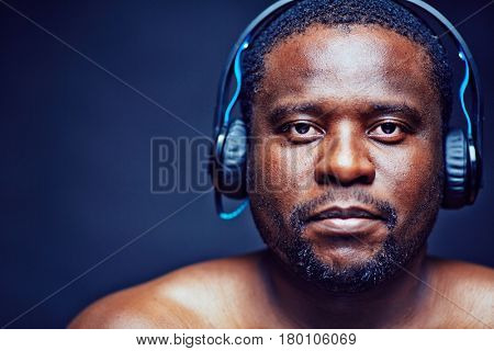 Head and shoulders portrait of bearded African American man looking at camera with serious face expression while listening to music in headphones