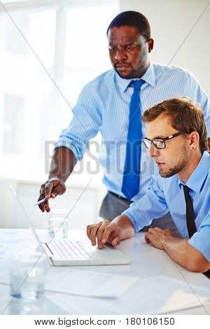 Dissatisfied African American boss pointing at mistake displayed on screen, bearded employee in eyeglasses sitting in front of laptop and making corrections
