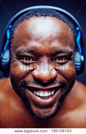 Portrait of cheerful African American music lover in headphones wrinkling nose and smiling from ear to ear while looking at camera