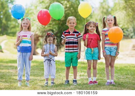 Happy children in summer wear standing in line on green lawn, holding colorful balloons and looking at camera