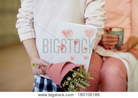Bunch of wildflowers and paper greeting-card behind girl back
