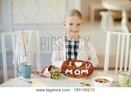 Happy child showing baked pie and looking at camera