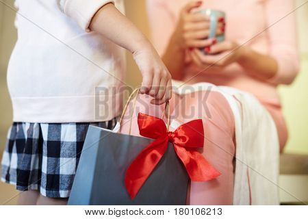 Little girl holding paperbag with red ribbon for her mother