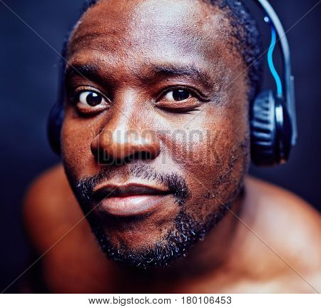 Close-up shot of middle-aged suspicious man looking closely at camera while listening to music in headphones against black background