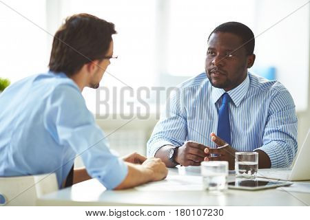 Portrait of confident middle-aged businessman holding negotiations with his partner while sitting in boardroom