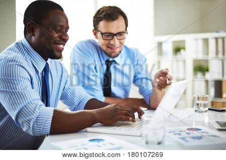Businesspeople having meeting in spacious boardroom: they looking at computer screen and discussing their joint project