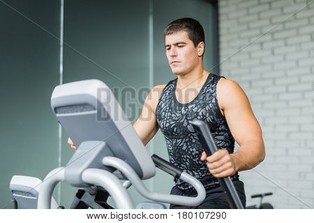 Portrait of muscular sportive man  running using elliptical trainer during workout in modern gym