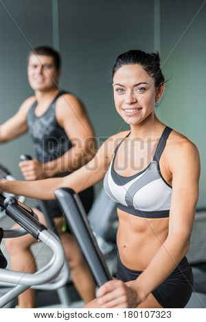 Portrait of beautiful  sportive brunette woman exercising using elliptical machine  next to fit man, both smiling looking at camera working out in modern gym
