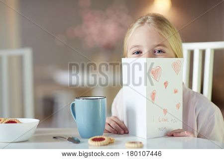 Curious girl peeking out of self-made paper greeting card for mom