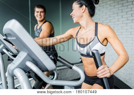 Portrait of beautiful  sportive brunette woman exercising using elliptical machine next to fit man and smiling to him during workout in modern gym