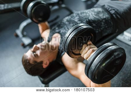 High angle view portrait of muscular man doing bench press exercise for chest muscles using heavy dumbbells in modern gym