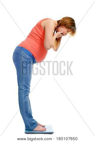 Pregnant woman on scales surprised by its weight isolated on white