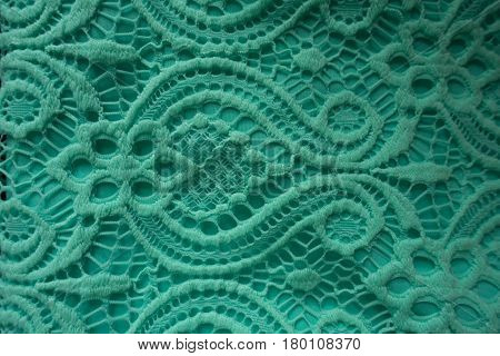 Close up of mint lace fabric with baroque pattern