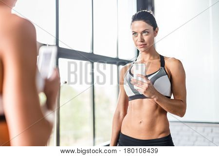 Portrait of pretty brunette woman smiling taking mirror selfie in gym,  posing boasting her fit figure and slim waist