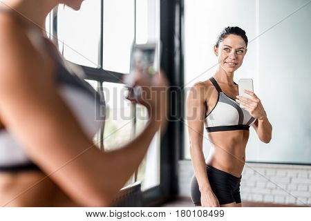 Portrait of proud muscular  woman boasting her fit figure and slim waist taking sefie in gym  mirror and posing after working out