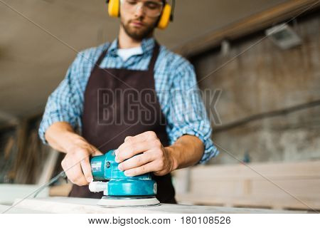 Close-up shot of male hands operating modern electric sander, carpenter looking at wooden work piece with concentration