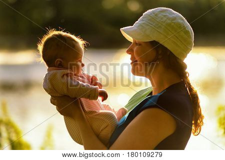 Mother hold her baby in nature at sunset