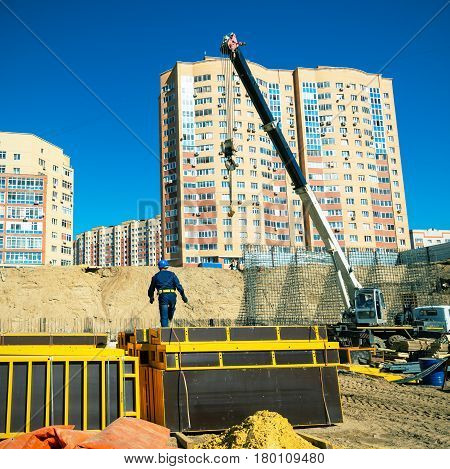 MOSCOW - MAR 27, 2014: Crane and worker working on a construction site.