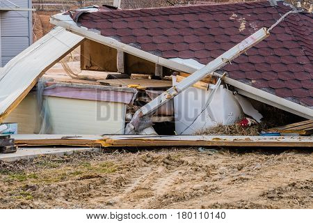 Shingled roof and other remains of a small house after being torn down by construction crew