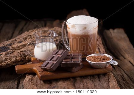 Cold Chocolate Milk drink and chocolate bar on wooden background.
