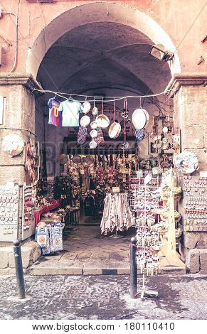 Naples, Italy - August 8, 2016: Traditional souvenir stall on the narrow street of Naples. Via dei Tribunali in the heart of Naples, one of the richest streets in history and monuments of tourists