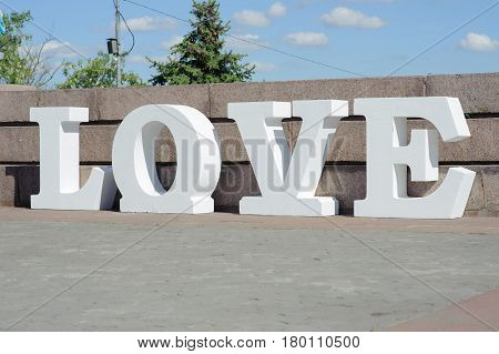 Modern volumetric white letters design on love featuring 3d typography. Letters on the asphalt.