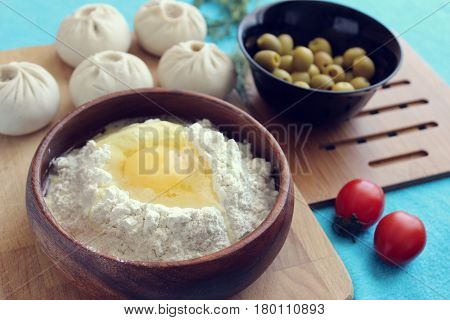 Buryat cuisine. Egg in flour, bouzou, greens, tomatoes on a bright, blue background