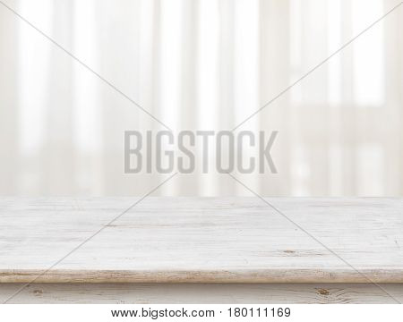 Wooden table on defocuced window with transparent curtain background