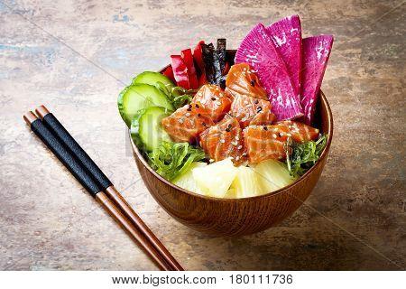 Hawaiian salmon poke bowl with seaweed watermelon radish cucumber pineapple and sesame seeds. Copy space background