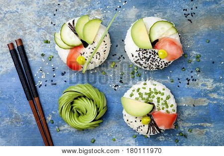 Vegan sushi donuts set with pickled ginger avocado cucumber chives nori and sesame on blue background. Sushi-food hybrids trend. Overhead top view flat lay.