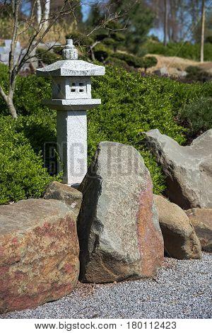 Stone lantern rock and raked gravel zen garden with evergeen box landscape design in Japanese style