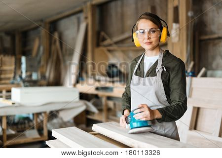 Confident fair-haired craftswoman in eye and ear protectors looking at camera while holding electric sander in hands, waist-up portrait